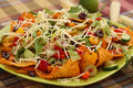 Nachos heap of with vegetables on green plate Stock Image