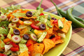 Nachos heap of with vegetables on green plate Royalty Free Stock Photo
