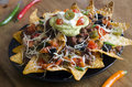 Nachos spicy with beef chilli peppers sour cream and guacamole Royalty Free Stock Images