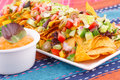 Nachos vegetables and cheese sauce on colorful towels Stock Image