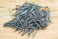 Nail fastener many nails lie on wooden boards Stock Photos