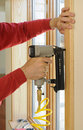 Nail gun being used to install wood trim around wi