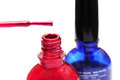 Nail polish bottles red and blue with red brush Royalty Free Stock Image