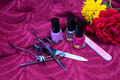 Nail polishes and manicure set with flowers on purple textile Royalty Free Stock Photography