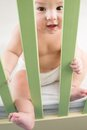 Naked baby in a diaper sitting in a crib and holding on safety fence Stock Image
