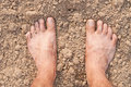 Naked feet on dry soil Stock Photography