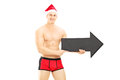 Naked guy wearing underpants and christmas hat holding an arrow red a big black pointing right isolated on white background Royalty Free Stock Photo