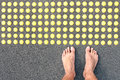 Naked human barefoot on asphalt road at tactile bumps pavin paving life concept of feeling with bare feet of blind people the Stock Photography