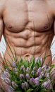 Naked man with bouquet of tulips Royalty Free Stock Images