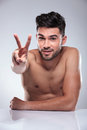 Naked man making the victory peace hand sign happy in studio Royalty Free Stock Photos