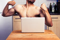 Naked man trying to impress during webcam chat young is in his kitchen and the person he s chatting online via by flexing his Royalty Free Stock Photos