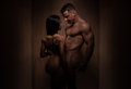 Naked romantic bodybuilding couple in silhouette portrait of a young posing front of a brown wooden wall while looking each other Royalty Free Stock Photo