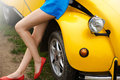 Naked and sexy legs of a girl sitting on a retro yellow car in summer Royalty Free Stock Photo