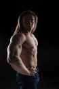 Naked torso male bodybuilder athlete with long blond hair in studio