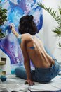 Naked woman back view working on watercolor painting of wall Royalty Free Stock Photo