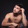 Naked young man looks up seated at the desk looking away from the camera while picking his hair on a black studio backgroud Stock Photos
