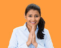 Namaste closeup portrait young woman praying looking at you in gratitude thankfulness and hope orange background positive human Royalty Free Stock Images