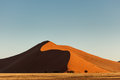 Namibian desert red sand dune in morning sun pyramid shaped dunes rise from grasslands on coast early this african is the oldest Stock Photography