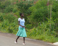 Nampevo mozambique december unknown girl african woma woman dressed in clothes is on the road in the plants Royalty Free Stock Photo