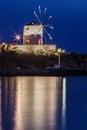 Naousa paros island greece the windmill lighten at night and iluminating the aegean sea Stock Photos