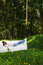 Nap in green forest young woman having on a white sofa Stock Photos