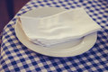 Napkin and plate on checkered table cloth a Stock Photography