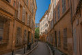 Narrow alley with buildings in the shadow in Aix-en-Provence. Royalty Free Stock Photo