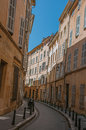 Narrow alley with tall buildings in the shadow in Aix-en-Provence. Royalty Free Stock Photo