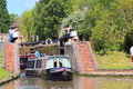 Narrow boat or barge in locks a traveling through lock gates that have just been opened a woman holding the gate open this was Stock Photos