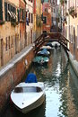 Narrow canal with bridge and boats  in Venice Royalty Free Stock Photo