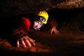 Narrow cave passage with a cave explorer Royalty Free Stock Photo