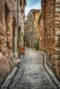 Narrow cobbled street with flowers in the old village France. Royalty Free Stock Photo