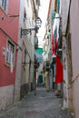 Narrow cobblestone alley street in alfama lisbon portugal with colorful laundry hanging from windows above Royalty Free Stock Image