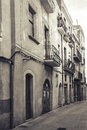 Narrow empty street view of tarragona vintage stylized monochrome photo with sepia toned filter effect and old photo paper texture Royalty Free Stock Photos