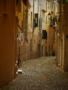 Narrow italian alley typical dark with drying laundry and bicycles Royalty Free Stock Images