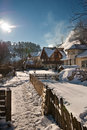 Narrow road covered by snow at countryside winter landscape with snowed trees road and wooden fence cold winter day at village Stock Photos