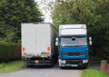 Lorries meeting on a narrow road. Royalty Free Stock Photo