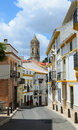 Narrow steep street in the ancient cordoba of spanish white town under spring sky Royalty Free Stock Photography