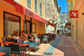 Narrow street with restaurants in menton june bars and shops on old part of town on french riviera popular resort tourists from Stock Photo