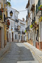 Narrow street sunlit over spring sky ancient spanish city granada Stock Photo