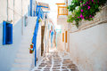 The narrow streets of greek island with blue balconies, stairs and flowers. Beautiful architecture building exterior Royalty Free Stock Photo