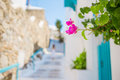 The narrow streets of greek island with flowers. Beautiful architecture building exterior with cycladic style. Royalty Free Stock Photo