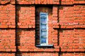 Narrow window in the red brick wall of the warehouse. Finland, national romanticism Royalty Free Stock Photo