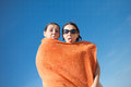 Nasty couple on the beach showing languages ​​on in an orange towel Royalty Free Stock Image