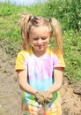 Nasty girl holding mud happy messy with on her face and ponytails Royalty Free Stock Image