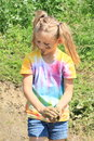 Nasty girl holding mud happy messy with on her face and ponytails Royalty Free Stock Photo