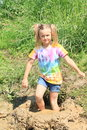Nasty girl in mud happy little colorful t shirt and blue shorts standing muddy puddle Royalty Free Stock Photo