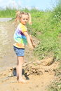 Nasty girl standing in mud happy little barefoot with ponytails playing Stock Photo