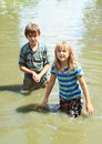 Nasty kids in clothes soaking wet in water girl and boy dirty of pond Stock Image