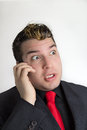 Nasty surprise young man in suit and tie talking on the phone with silly expression Stock Image